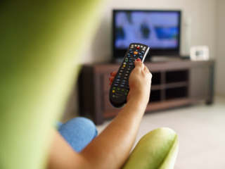 Person pointing remote at television.
